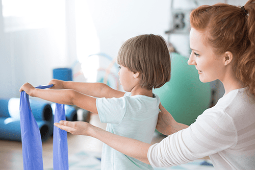 physiotherapist-supporting-kid-PFSENG9